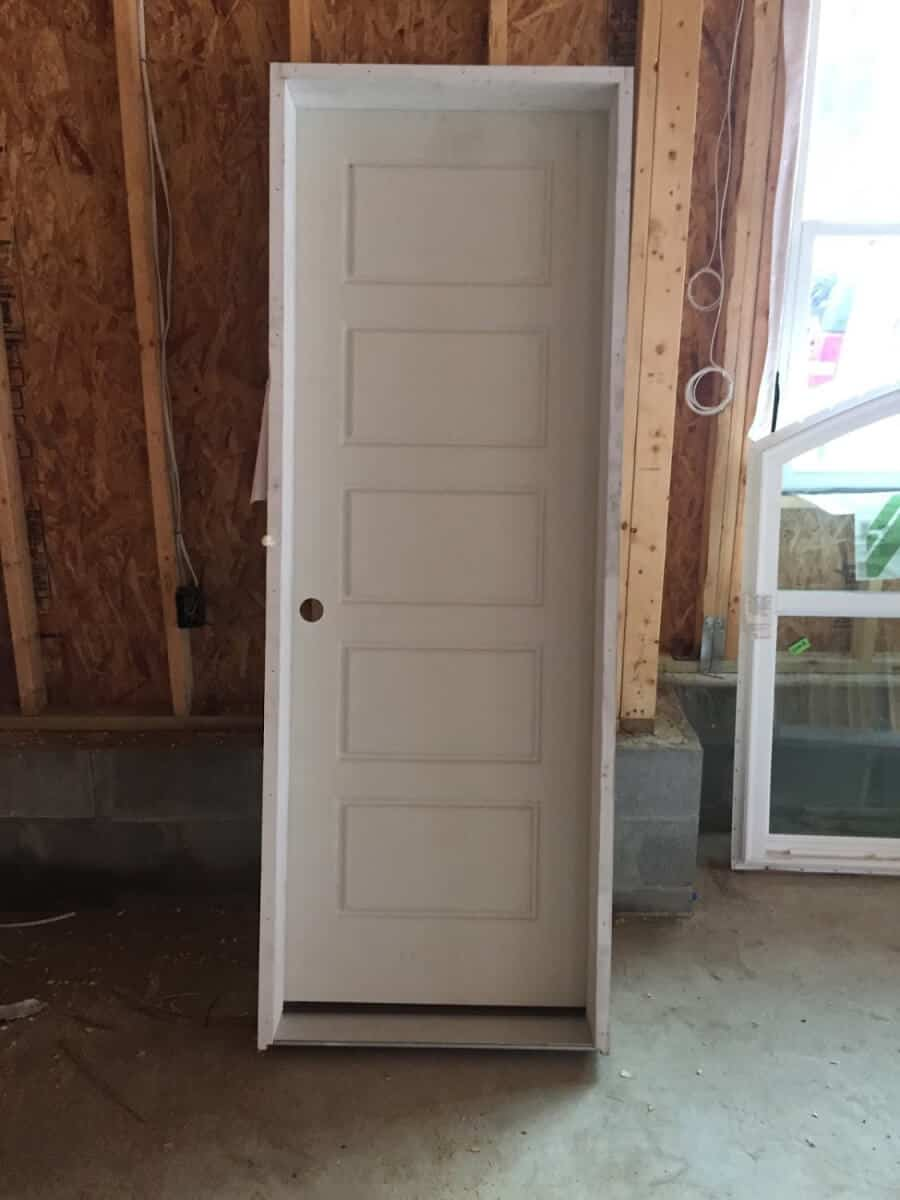 Interior farmhouse door with five panels on it. Sitting inside a garage.