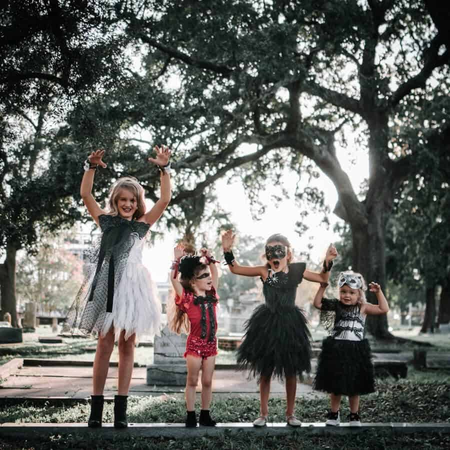 Four girls in a cemetery dressed up for Halloween