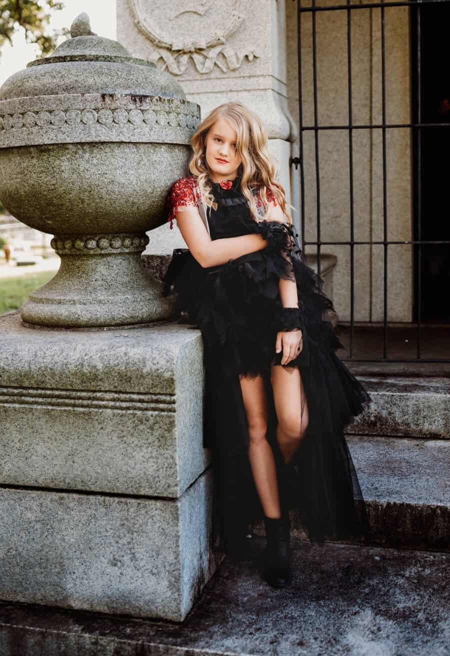 Girl in Halloween costume in old cemetery.