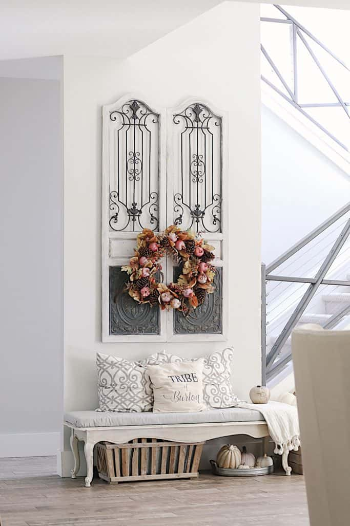 Front foyer with a Fall wreath hanging on gates on a wall. With a bench below it.