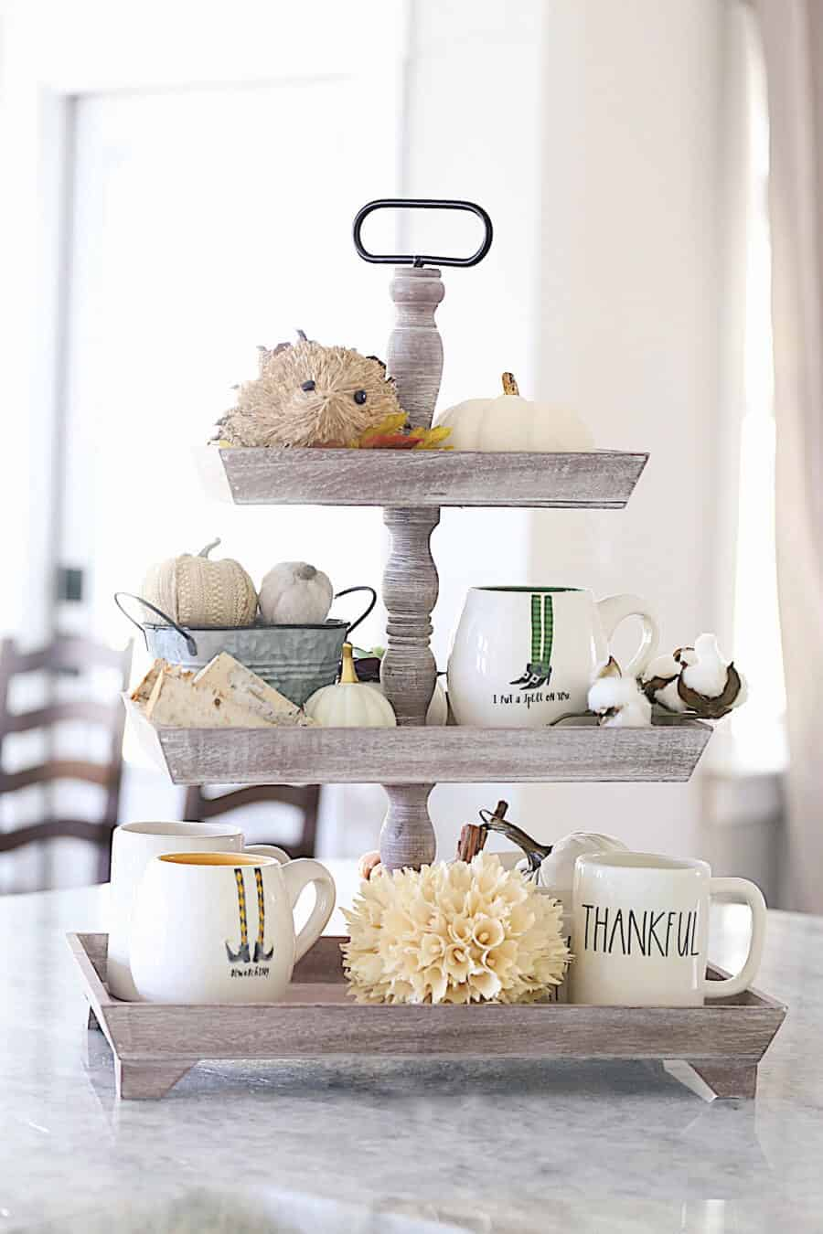 A 3 tier tray with Rae Dunn Mugs and cotton and fall decor