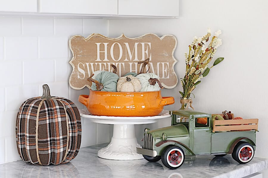 Home Sweet Home sign on a kitchen counter with a vintage truck full of Pumpkins.