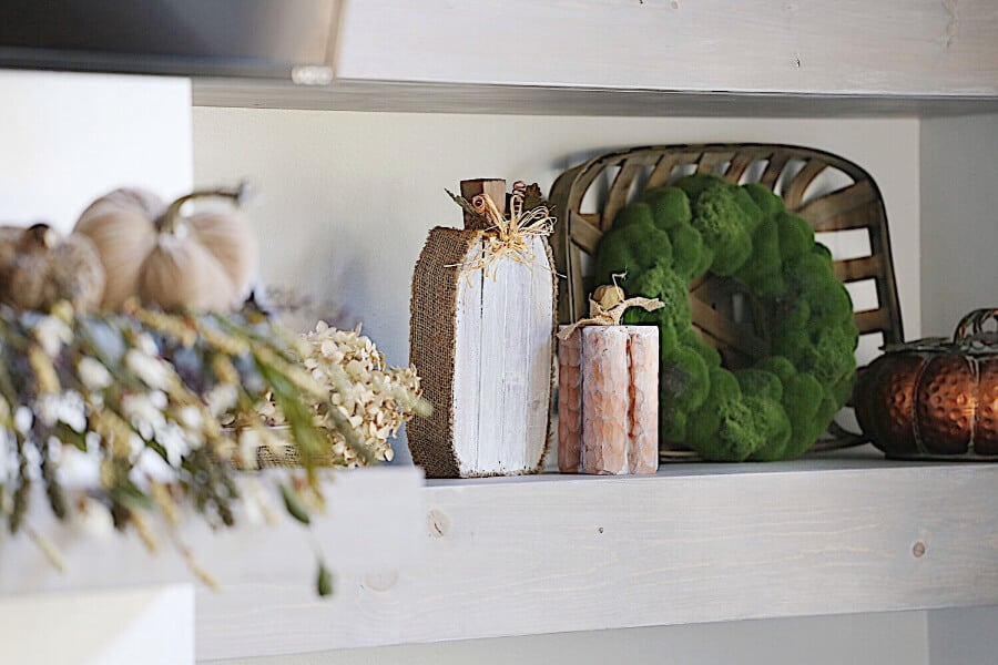 An open shelf on the wall with pumpkins that are wood and metal.