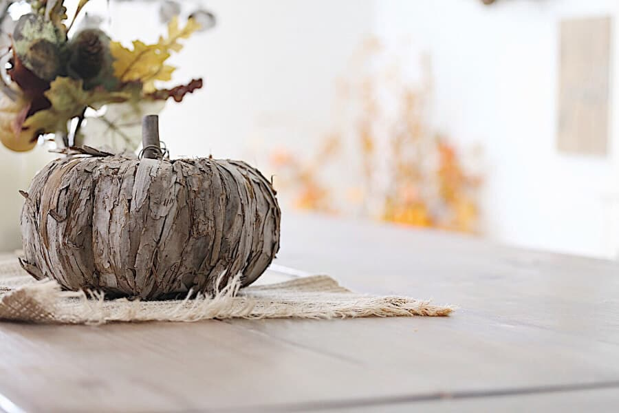 A wooden farmhouse table with wooden pumpkins
