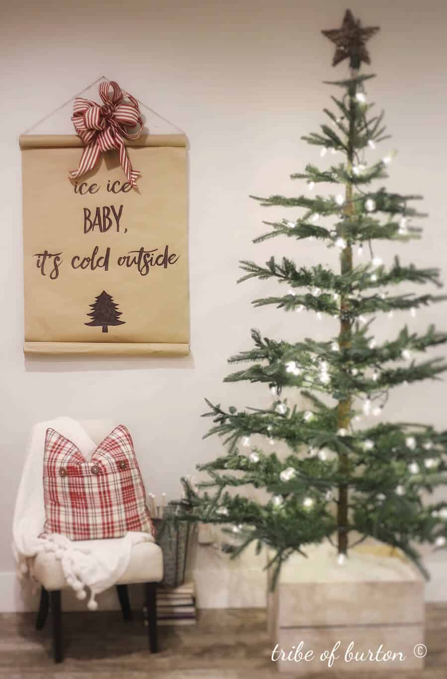 Christmas tree with a craft scroll on the wall with a big red bow.