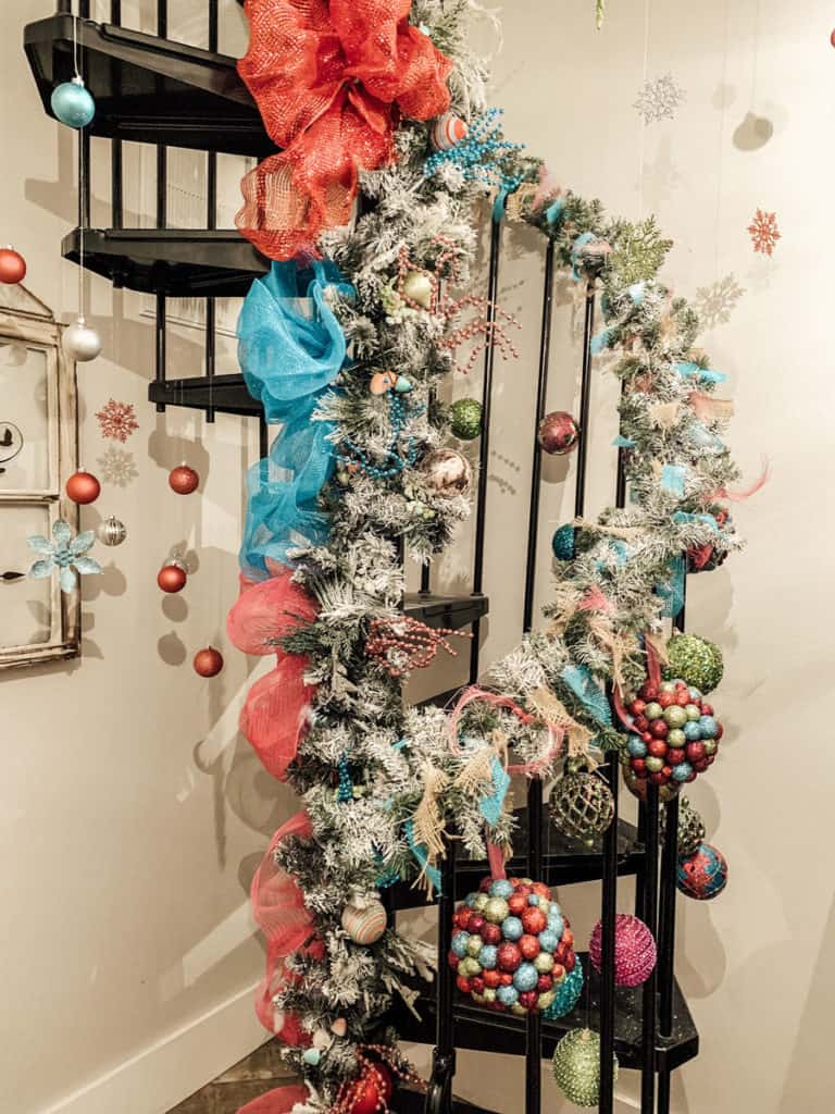 Black Spiral Staircase Wrapped in Garland with Pink and Blue Decor