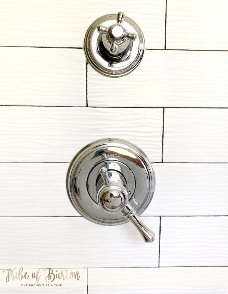 Grey grout lines on white tile of bathroom shower.