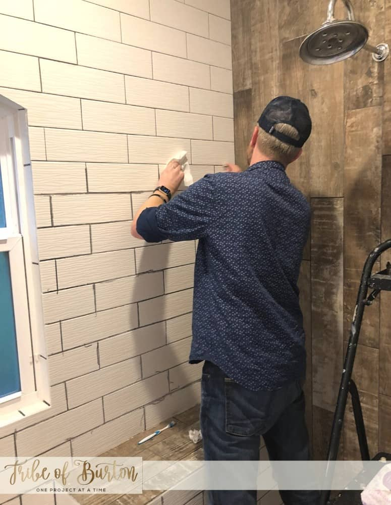 Man coloring bathroom shower grout lines grey.