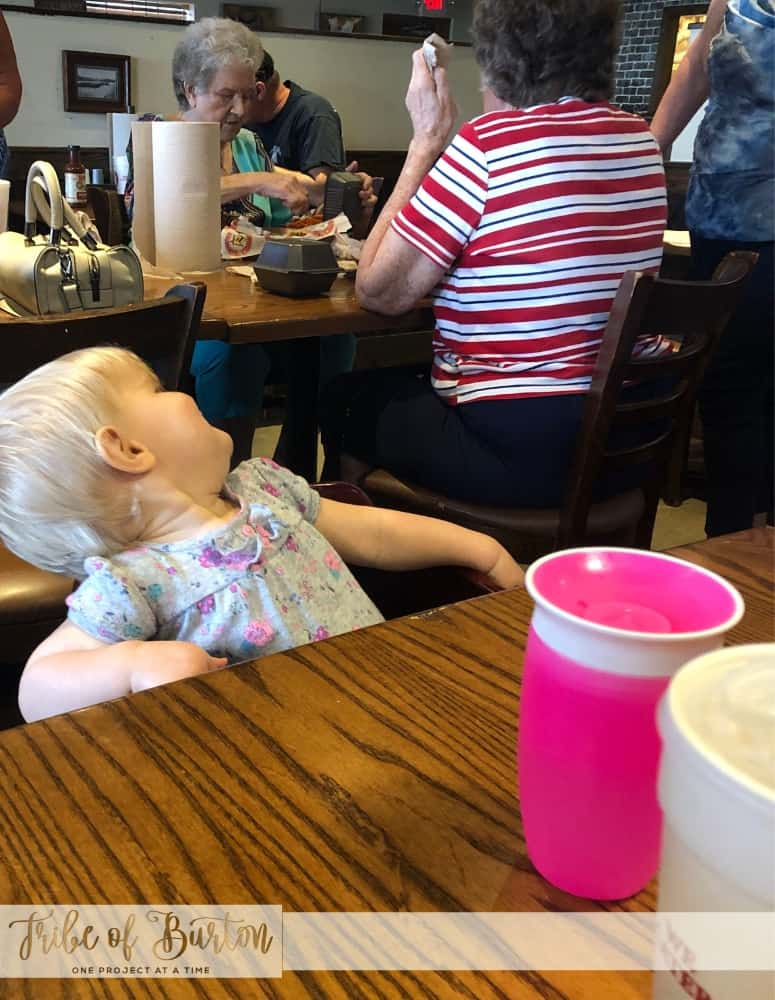 Baby in a highchair at a restaurant. Ladies at a table behind her. Pink sippy cup on table.