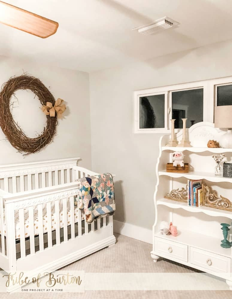 A baby crib and old quit with a wreath on the wall and a bookshelf.