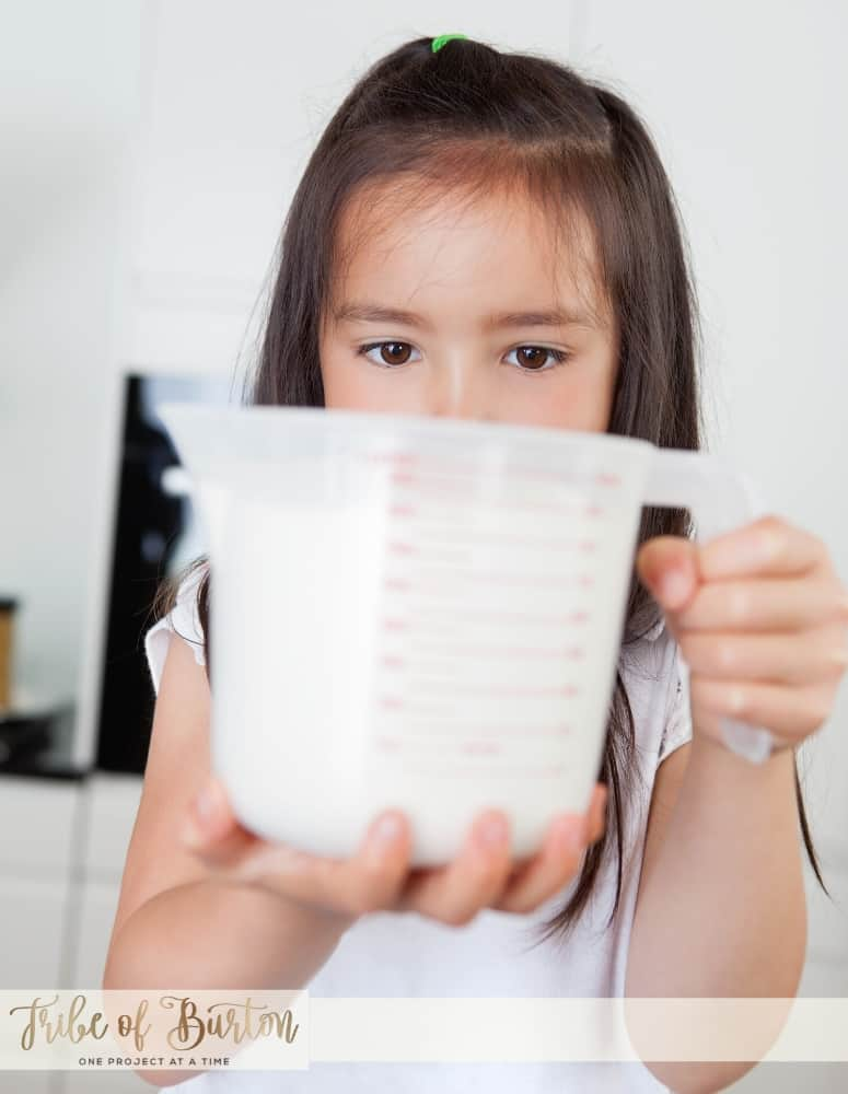 A little girl with a measuring cup