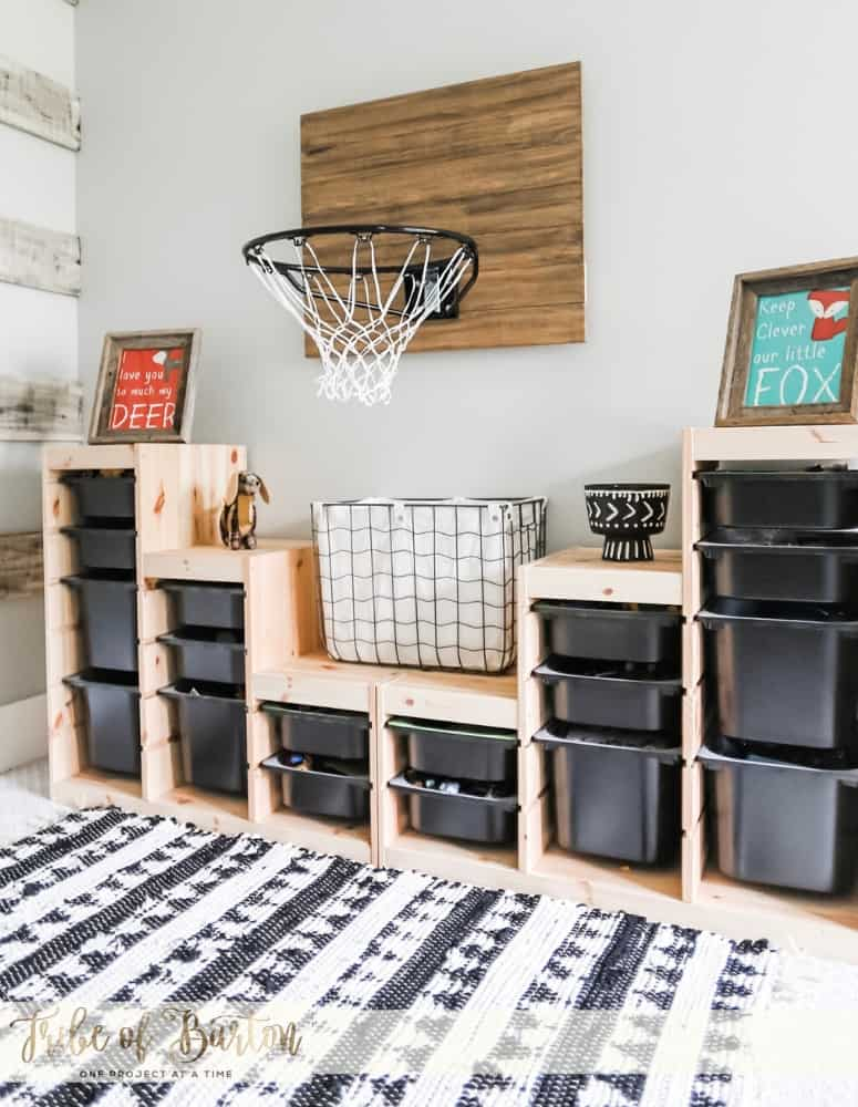 Black Plastic Toy Storage bins on a wooden shelf with a basketball hoop and a black and white rug