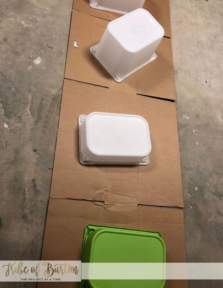 Plastic toy bins upside down laying on cardboard in a garage floor.
