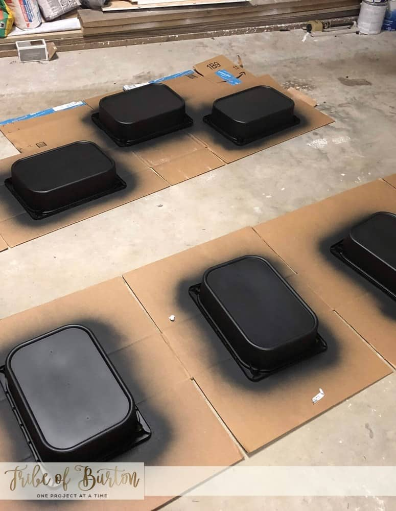 Black plastic painted buckets laying upside down on cardboard drying in a garage.